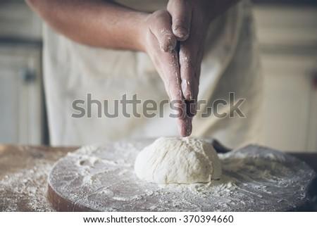 Man baking bread in the kitchen. - stock photo