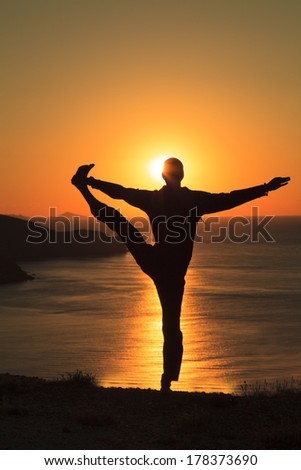 Man balance in yoga tree pose on ocean beach at sunset