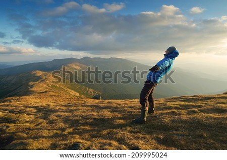 Man balances. Strong wind in the mountains. Autumn Landscape - stock photo