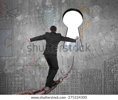Man balancing on old iron chain toward keyhole, with cityscape view and business concept doodles wall background - stock photo