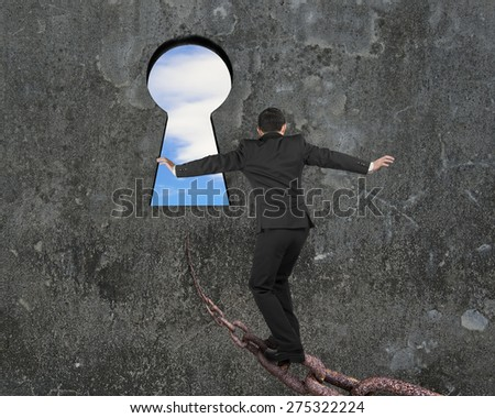 Man balancing on old iron chain toward keyhole, with sky clouds view and gray concrete wall background - stock photo