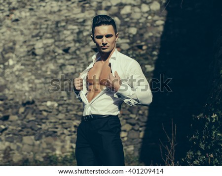 Man bare-chested young handsome sensual model wears shirt trousers looks forward outside grey color filtre on masonry background