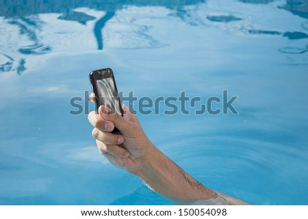 man bathing in a pool with your  smartphone mobile phone  without getting wet - stock photo