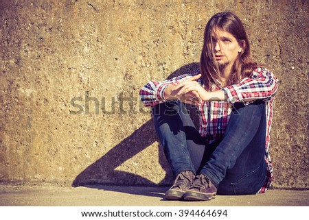 Man bearded long hair sitting sad alone by grunge wall outdoor. Unemployment depression or sadness concept. - stock photo