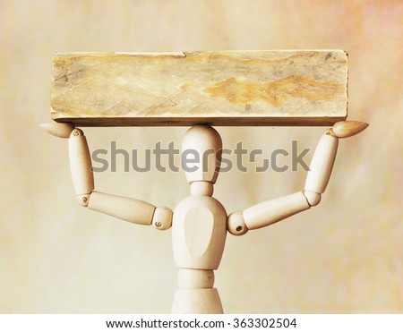 Man bearing heavy load over its head. Abstract image with a wooden puppet - stock photo