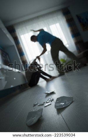 Man beating the woman on the floor - stock photo