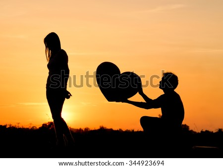 Man begging a woman for love by giving a big heart - stock photo