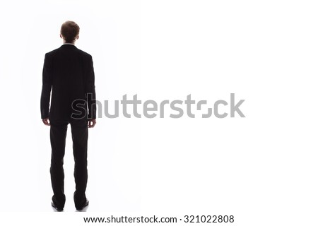 MAN BEHIND on a light background.BODY BACK. A handsome man in a black suit and tie to his full height, he stands with his back to the camera on a light background.MAN BEHIND - stock photo