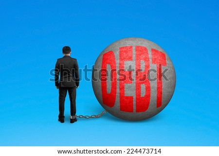 man being trapped with debt ball isolated on blue - stock photo