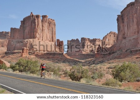Man Biking at Three Gossips, and Rocky Formations at Arches National Park in Utah, USA - stock photo