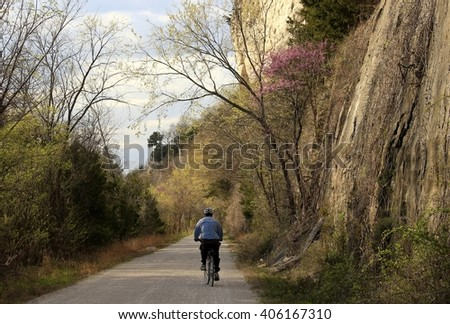 Man biking by the bluffs of the Missouri River in the spring - stock photo