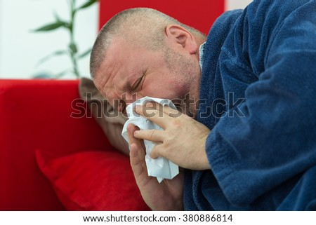 Man blowing his nose in his living room - stock photo
