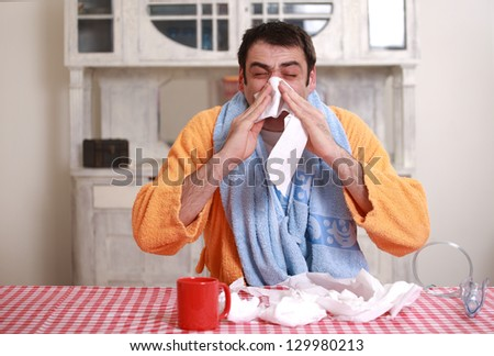 Man blowing his nose  into tissue paper