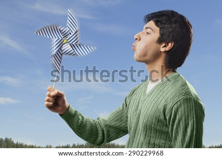 Man blowing on a pinwheel - stock photo