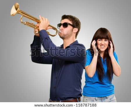 Man Blowing Trumpet In Front Of Frustrated Woman On Gray Background - stock photo