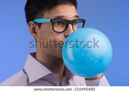 Man blowing up balloon on blue background. portrait of young man blowing blue balloon - stock photo