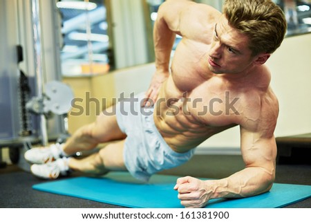 Man bodybuilder does exercise lying on one side and leaning on elbow, forearm and feet - stock photo