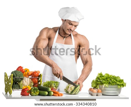 Man bodybuilder in white toque blanche and cook protective apron, concoction vegetables and fruit , on whie background, isolated - stock photo