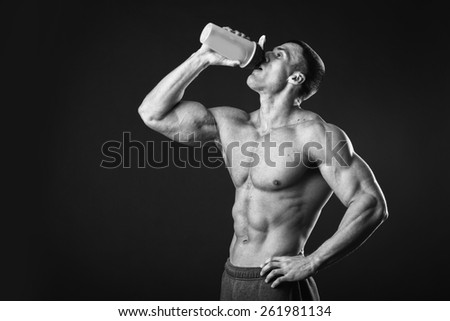 Man bodybuilder posing on gray background Man is holding a shaker for drinks. Man drinking a protein shake, water, amino acids from the shaker. Sports, sports nutrition, food additive. - stock photo