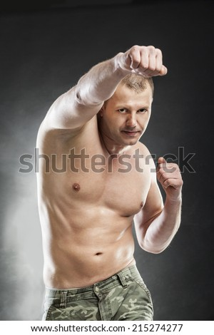 man boxing half naked on gray background