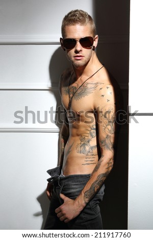 Man, boy, guy .Handsome tattooed man with no shirt touched by the woman's hand  - stock photo