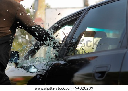 Man breaking a car's window in a million of pieces - stock photo