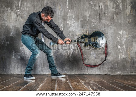 man breaking guitar on the floor - stock photo