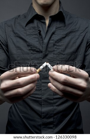 Man breaks cigarette - smoking cessation concept - stock photo