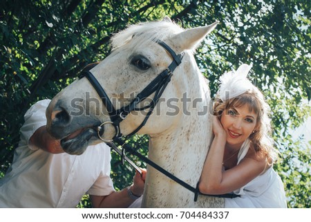 Man, bride and white horse in the park among green trees