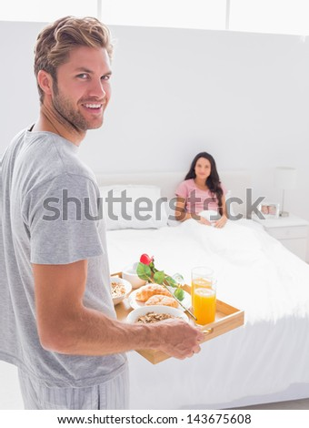 Man bringing breakfast to his wife at bed - stock photo