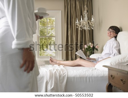 Man bringing coffee to wife in bed