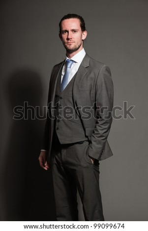 Man brown long hair with expressive face wearing grey suit and blue tie. Isolated on grey background.