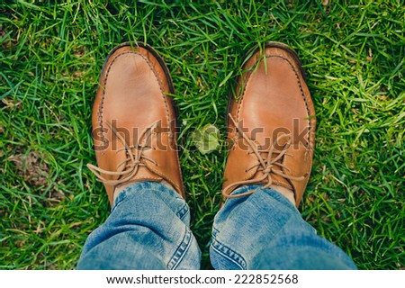 man  brown shoes  on the green grass outdoors