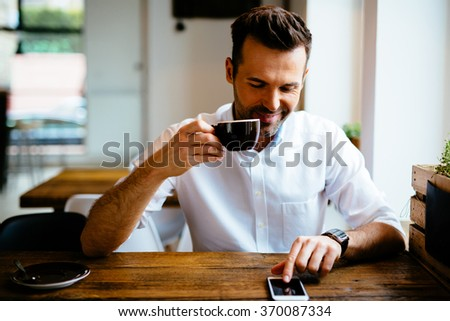 Man browsing internet on smartphone and drinking cappucino at coffee shop