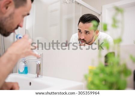 Man brushing his teeth in bathroom - stock photo