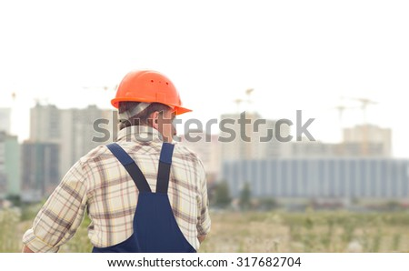 Man builder on the background of buildings under construction. A man in a construction orange helmet on his head standing with her back to the camera. A man in a half-turn. - stock photo