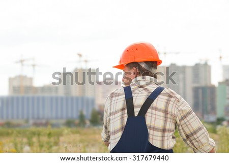 Man builder on the background of buildings under construction. Man in a construction orange helmet on his head standing with her back, half-turn. Sad male construction worker, he was tired at work. - stock photo
