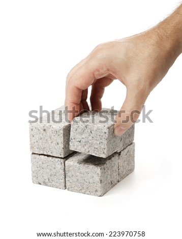 Man building a cube of smaller cubes made of granite rock. - stock photo