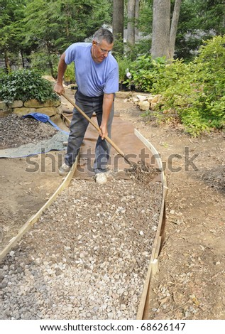 Man building gravel path with wood edging - stock photo