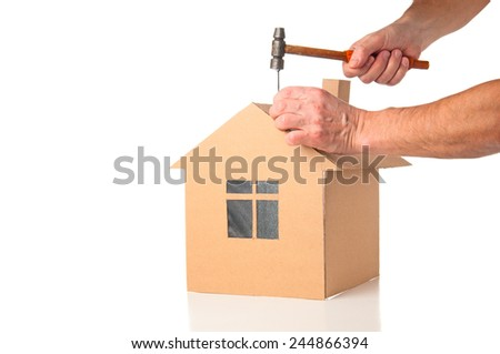 Man builds cardboard model of a house - stock photo