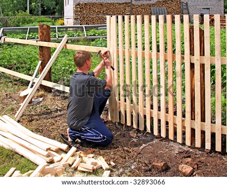 Man builds fence stock photo