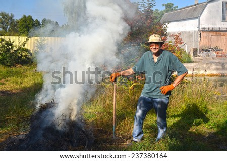 Man burn out dry grass in the garden.Ukraine