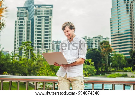 Man businessman or student in casual dress using laptop in a tropical park on the background of skyscrapers. Dressing in a white shirt, beige shorts. Mobile Office concept.