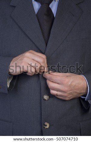 man buttoning his jacket