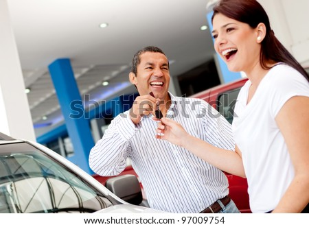 Man buying a car for his wife and handling her the keys - stock photo