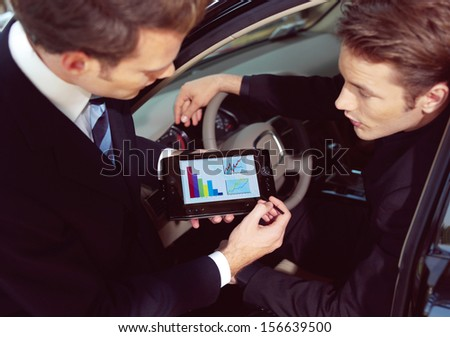 Man buying a car in dealership sitting in his new auto, the salesman talking to him and explaining details on laptop - stock photo
