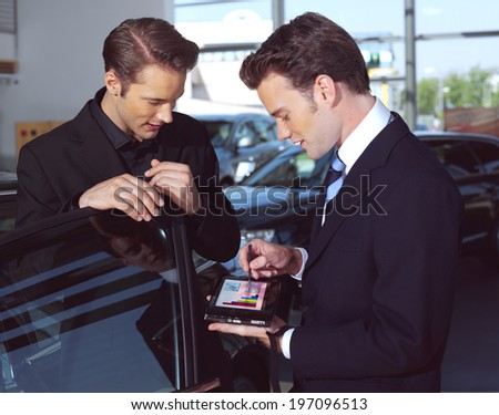 Man buying a car, the salesman talking to him and explaining details on laptop