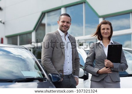Man buying a new car in a garage - stock photo