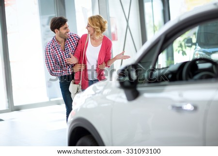 Man buying car to his wife, happy surprised woman looking in her husband  - stock photo