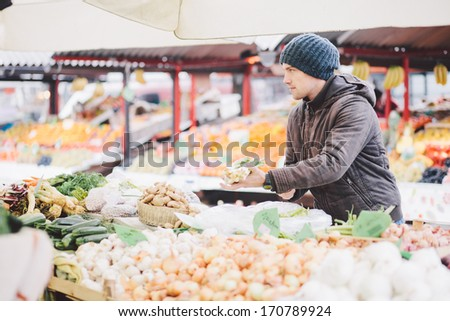 Man buying fresh vegetables at farmer's market - stock photo